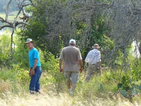 Braving the chiggers to plot the path for the pipes (Jerry, George and Mike) (Courtesy of Paula Richards)