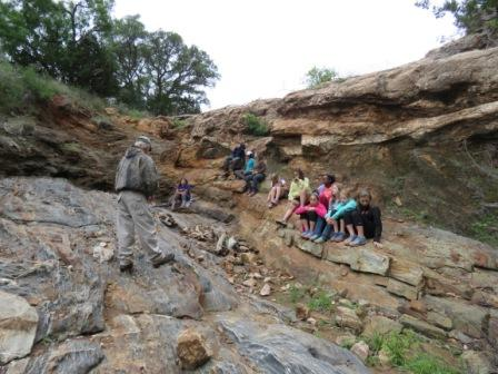 5th graders sitting on Billion year old rocks as Billy Hutson explains the uniqueness of hill country geology.  (Courtesy of Alice Rhueme)