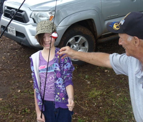 Phil Wyde gives a little help with baiting the hook. (Courtesy of Paula Richards)